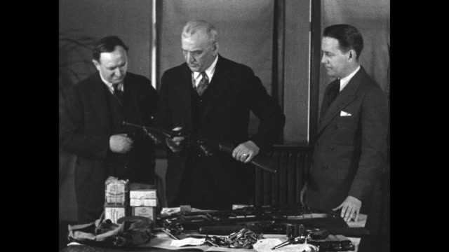 three men behind table with guns confiscated from hideout of career criminal basil banghart; man in middle holds machine gun / revolver in man's... - mug shot stock videos & royalty-free footage