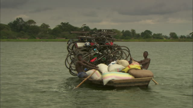 Three men carry a large number of bicycles on a rowing boat as they cross the Zambezi River.