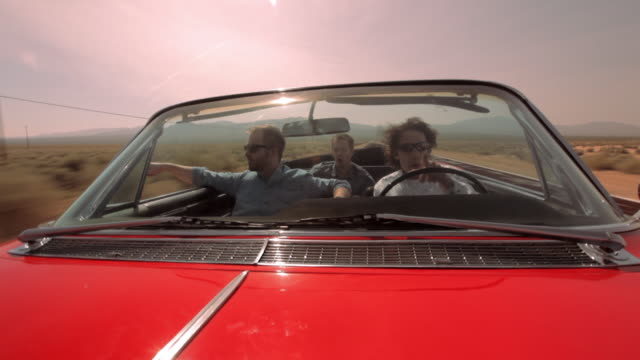 vídeos y material grabado en eventos de stock de three men cruise down a desert highway in a red vintage convertible. - pasear en coche sin destino