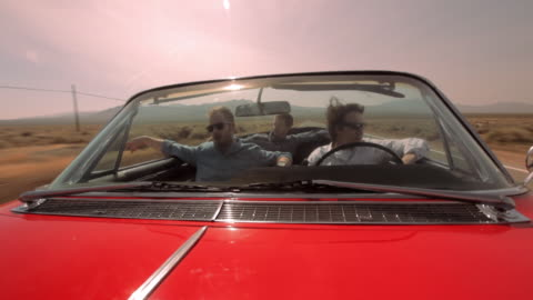 three men cruise down a desert highway in a red vintage convertible. - vorderansicht stock-videos und b-roll-filmmaterial