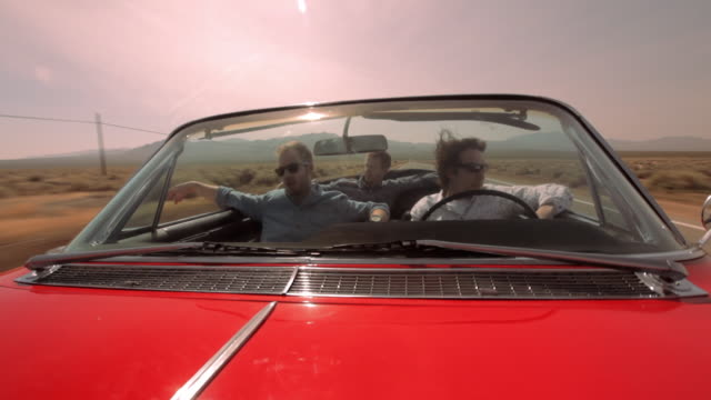 three men cruise down a desert highway in a red vintage convertible. - vorderansicht stock-videos und b-roll-filmmaterial