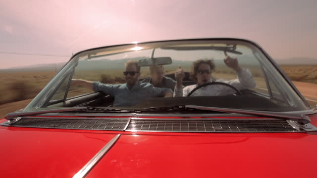 three men cruise down a desert highway in a red vintage convertible. - collector's car stock videos and b-roll footage