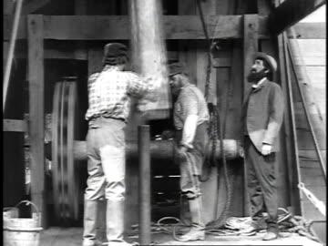 1923 reenactment three men drilling an oil pipe into the ground / united states  - oljepump bildbanksvideor och videomaterial från bakom kulisserna