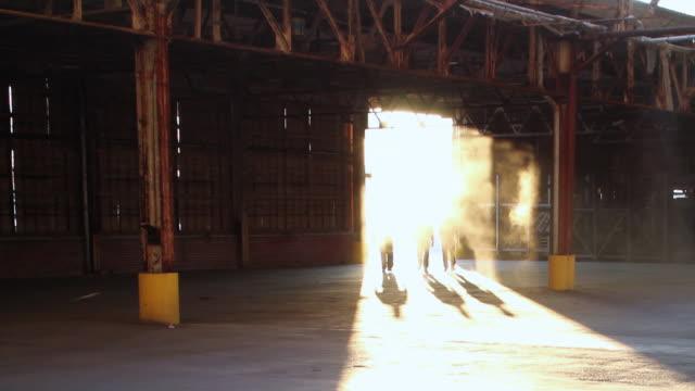 WS Three men entering warehouse though dust-filled doorway / Jacksonville, Florida, United States