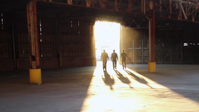 WS Three men entering warehouse through doorway / Jacksonville, Florida, United States
