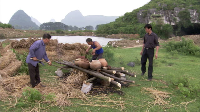 Three men fire clay pots. Available in HD
