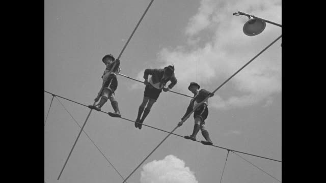 ws three men getting ready to walk on tightrope lagoon in background / close view from below of two men walking on tightrope supporting man rotating... - chicago world's fair stock videos and b-roll footage