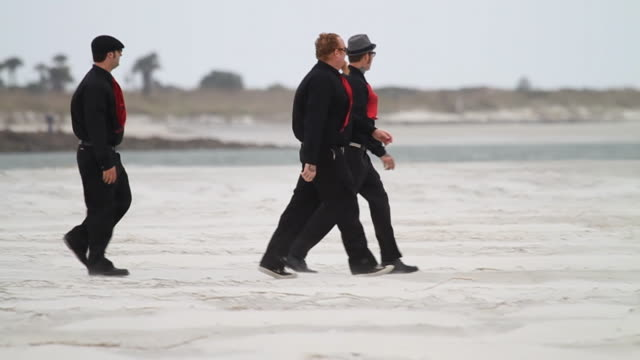slo mo ws pan three men in black clothes and red ties walking across beach / jacksonville, florida, usa - schwarzes hemd stock-videos und b-roll-filmmaterial