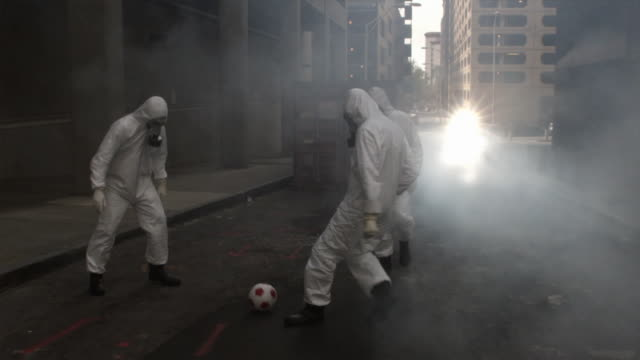 SLO MO WS Three men in HAZMAT suits and gas masks playing soccer on street, Atlanta, Georgia, USA