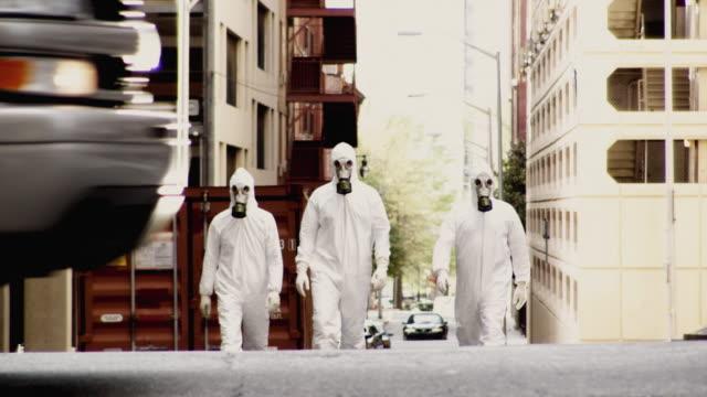 ws td three men in hazmat suits walking along street, atlanta, georgia, usa - gas mask stock videos & royalty-free footage