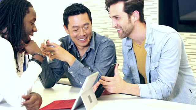 事務所話デジタル タブレットを使用の三人男 - 談笑する点の映像素材/bロール