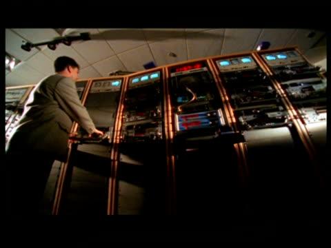 stockvideo's en b-roll-footage met ms, pan, la, three men in video control room - letterbox format