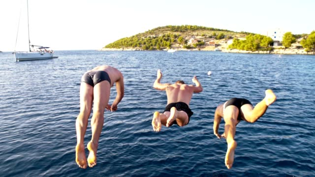 SLO MO Three men jumping into the sea