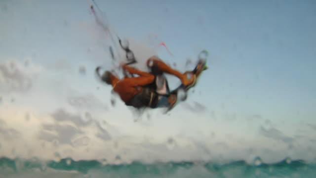 vídeos de stock, filmes e b-roll de la ws pan three men kiteboarding in caribbean sea as wave splashes camera / tulum, mexico - tulum méxico