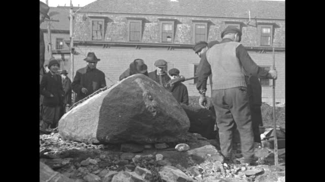 three men look over a boulder with an incised '1620' / men dig around the base of the rock and wave their hats / a man's hand traces a new crack in... - massachusetts stock-videos und b-roll-filmmaterial