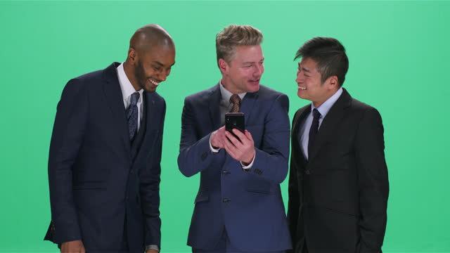 three men looking at smartphone and smiling , greenscreen - full suit stock videos & royalty-free footage