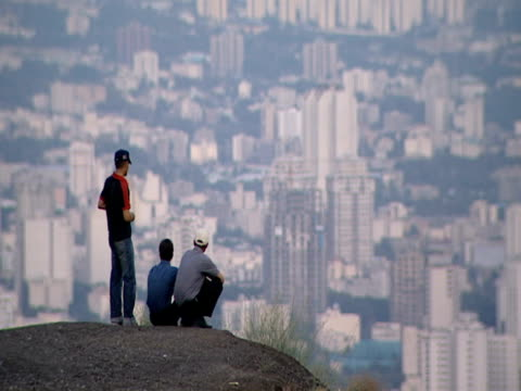 ha three men looking out onto the expansive cityscape from an elevated vantage point / tehran, iran - teheran video stock e b–roll