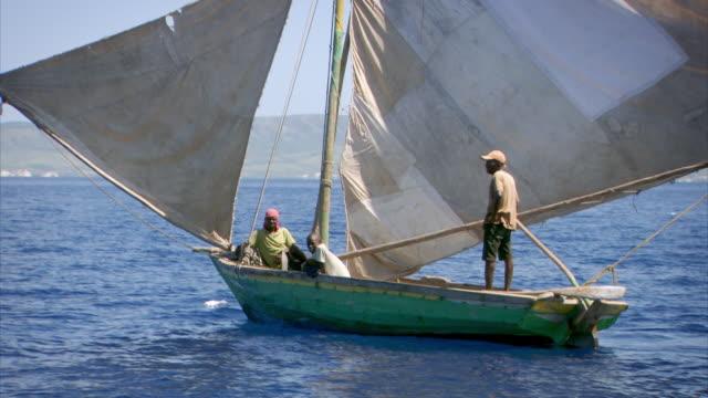 Three men luxuriate on a wooden sailing boat, Haiti.