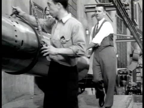 three men moving pushing hanging torpedo ws men working in torpedo warehouse man working on propellers man woman working on torpedo fg wwii - weapon stock videos & royalty-free footage