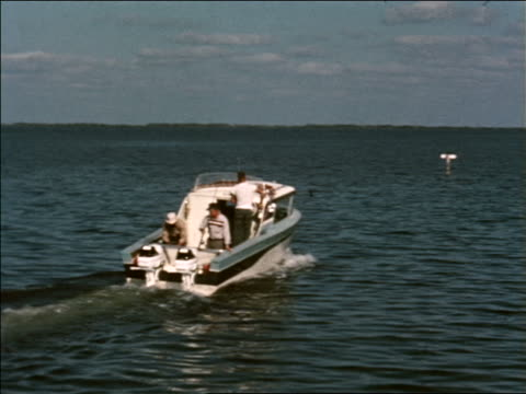 1963 REAR VIEW three men on boat going out for deep sea fishing / industrial