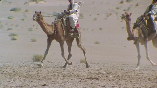 sm ws reenactment three men on camels riding through desert/ iran - ラクダ点の映像素材/bロール