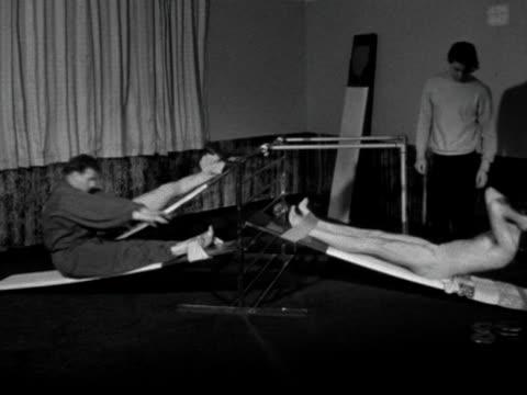 three men perform situps in a gym - allenamento a corpo libero video stock e b–roll