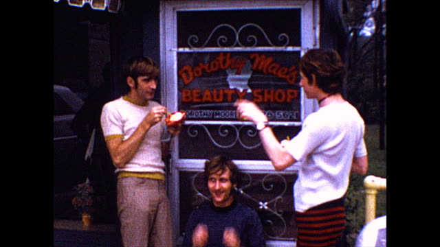 """three men primp their hair in front of a salon. zoom of the """"queen"""" in the dairy queen sign. a man finishes his sundae. - body care stock videos & royalty-free footage"""