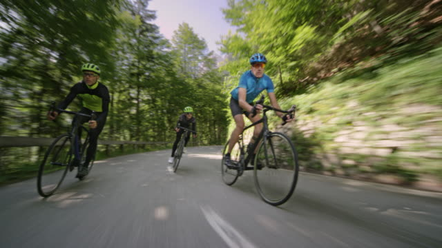 three men riding road bikes down an asphalt mountain road on a sunny day - all shirts stock videos & royalty-free footage