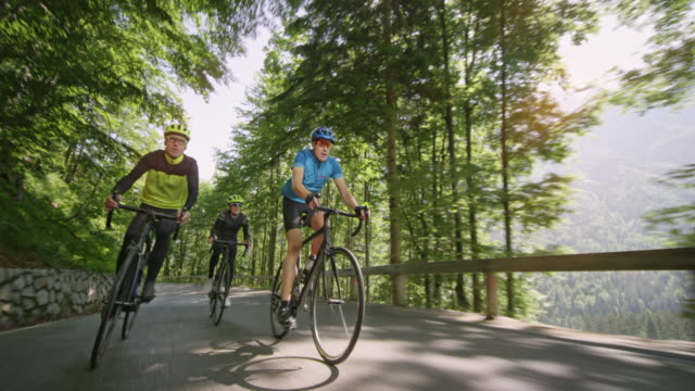 three men riding road bikes up an asphalt mountain road on a sunny day - mountain pass stock videos & royalty-free footage