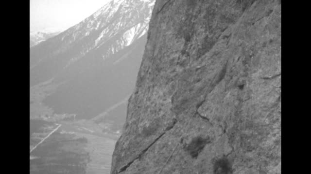 three men roped together and four men roped together walk up narrow alpine path toward camera / from behind three men traverse treacherous path /... - alpi video stock e b–roll
