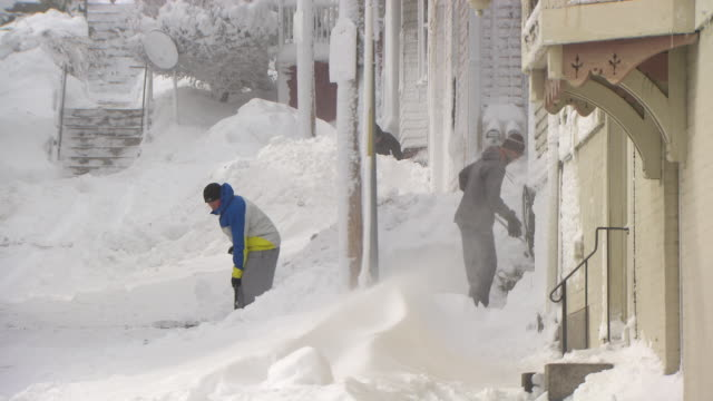 vidéos et rushes de three men shoveling snow with big snow drifts and wind blowing - neige fraîche
