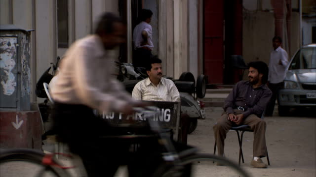 Three men sit and watch traffic.