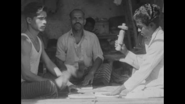 Three men sitting crosslegged use small mallets to shape silver paper / Muslim man in fez examines bracelet as Hindu jewelers look on / seated man...