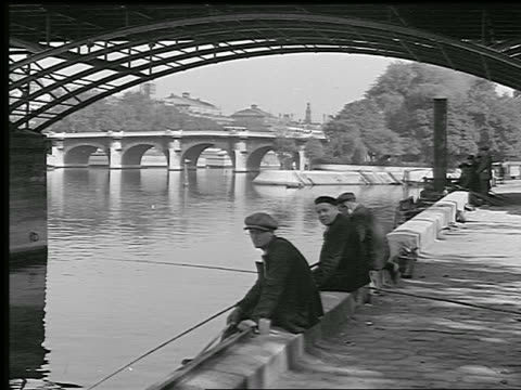 b/w 1936 three men sitting on side of seine river under bridge fishing / pont-neuf in background / paris - river seine stock videos & royalty-free footage