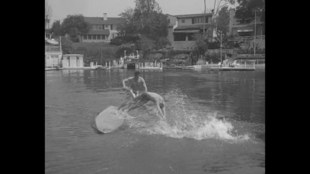 VS three men squat stand and dive off Motorboard as it moves around small private Toluca Lake houses docks and trees stand on shore / Note exact day...