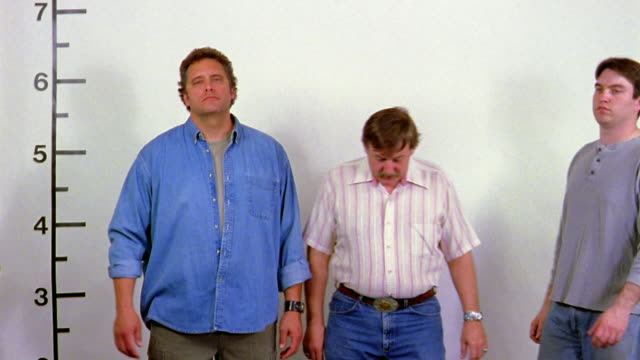 Three men stand in front of a white wall in a police lineup.
