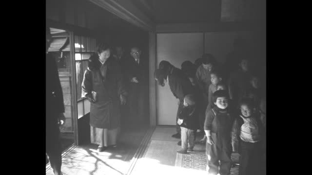 vidéos et rushes de three men stand outside entrance to tokyo orphanage awaiting arrival of empress nagako / car carrying empress turns into lane and drives towards... - orphelin