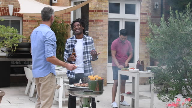 Three men standing in garden having barbecue and laughing