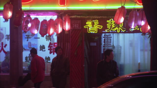 vídeos de stock, filmes e b-roll de ms three men standing outside restaurant on busy street at night , beijing, china - língua chinesa