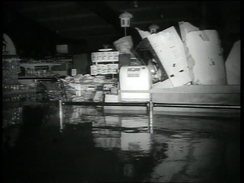 three men wading through thigh-deep water in front of supermarket / litter floating in flooded supermarket interior / three men leaving market... - telefonzelle stock-videos und b-roll-filmmaterial