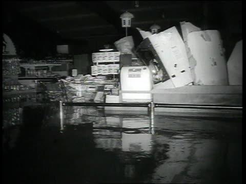 three men wading through thighdeep water in front of supermarket / litter floating in flooded supermarket interior / three men leaving market pushing... - telefonkiosk bildbanksvideor och videomaterial från bakom kulisserna