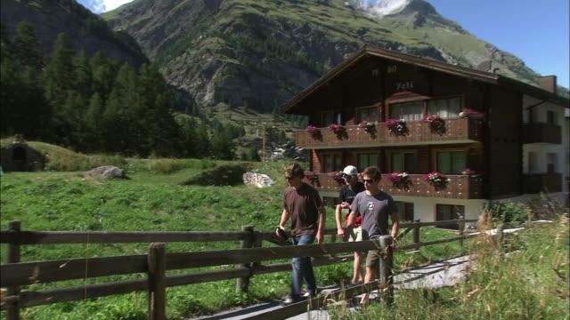 Three men walking on the boardwalk In Switzerland