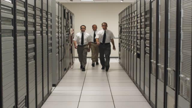 vídeos de stock e filmes b-roll de slo mo ws three men walking toward camera in server room corridor, dallas, texas, usa - grande sistema informático