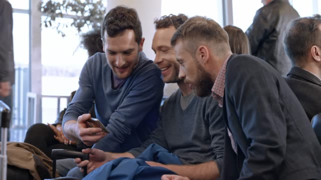 three men watching something on the smartphone and laughing as they wait for boarding at the airport - ridere video stock e b–roll