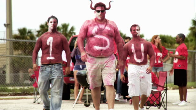slo mo ms td three men wearing body paint to celebrate sporting event approaching camera, jacksonville, florida, usa - body paint stock videos & royalty-free footage