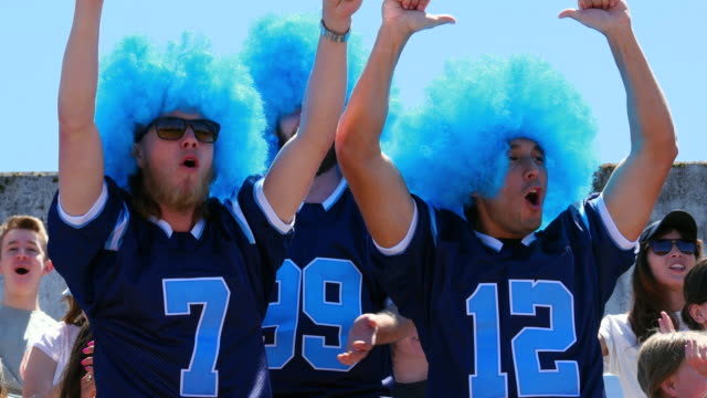 MS Three men wearing football team jerseys and wigs cheering for team in stadium stands