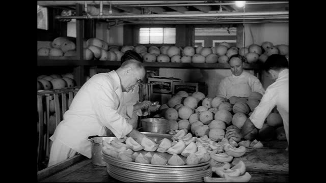 stockvideo's en b-roll-footage met hd ws three men working in prep kitchen choosing cantaloupe melons from large pile on table quartering cleaning seeds placing melon slices on large... - 1949