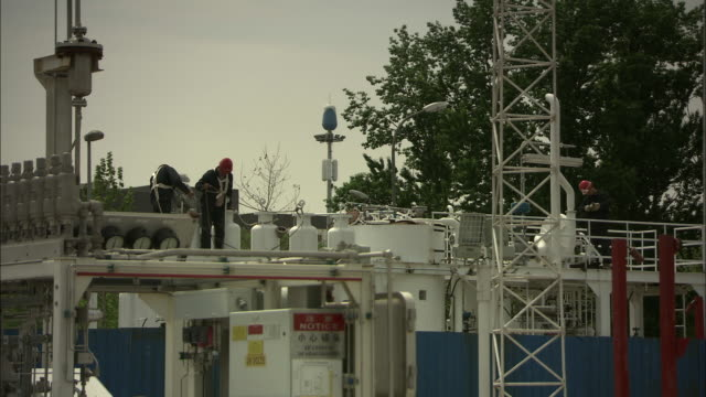 WS Three men working in systems area of hydrogen fuel pump station, Beijing, Beijing, China