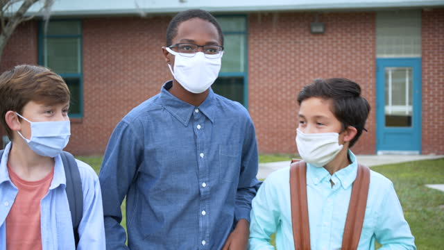 three middle school boys walking, talking outdoors, in masks - 12 13 years stock videos & royalty-free footage