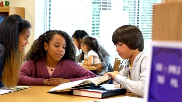 vídeos de stock e filmes b-roll de three middle school friends studying together in library - aluna da escola secundária
